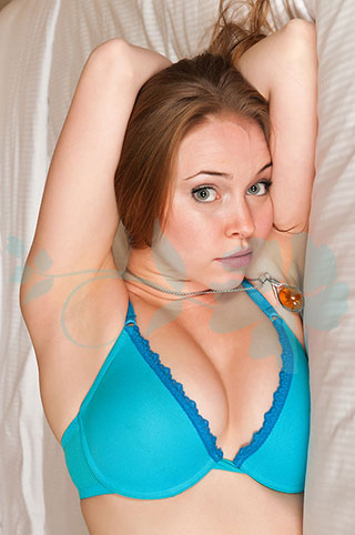 Redhead with nose piercing poses on her side on the bed.