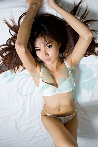 Slender waisted Asian poses on the bed in white lingerie.